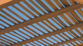 Een houten luifel tegen een duidelijke hemelachtergrond op een zonnige dag Meetkunde in ruimte, snijdende lijnen Schaduwen van Ge stock videobeelden