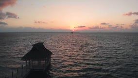 Een houten pijler of een gang met een palapa aan het eind bij een vakantietoevlucht dichtbij Cancun, Mexico bij zonsopgang stock video