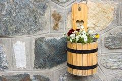 Een houten pot van bloemen hangt op steenmuur Stock Afbeeldingen