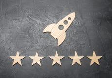 Een houten ruimteraket en vijf sterren op een concrete achtergrond Het concept ruimtevaart, commerciële lanceringen in ruimte royalty-vrije stock foto