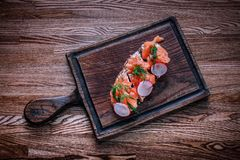 Een houten tafelblad waarop een raad van sandwiches met salmo ligt stock fotografie
