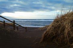 Een houten trap leidt tot een zwart vulkanisch zandstrand op de kusten van de Atlantische Oceaan stock afbeelding