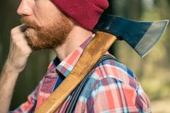 Een houtvester met een rode baard met een bijl op zijn schouder loopt thr royalty-vrije stock fotografie