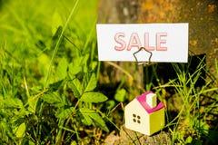 Een huis adverteert a voor het Gebruik van het verkoopteken het voor een woningmarktconcept Huislening, hypotheken, schuld, bespa stock foto's