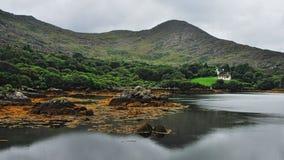 Een huis bij het meer in Iers platteland stock foto's