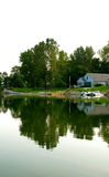 Een huis dat een meer wordt overdacht Stock Afbeelding