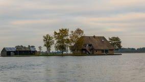 Een huis in Giethoorn, Nederland, dat op waterkanalen wordt gefotografeerd op een dalingsdag, met groen gras, en speciale archite stock fotografie