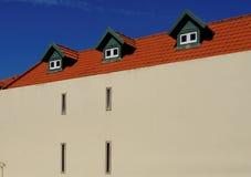 Een huis met rood tegeldak en drie zolderkamers Stock Afbeelding