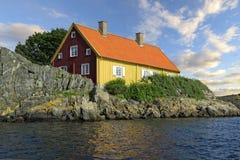 Een huis rood en geel enkel dicht bij het water stock afbeelding