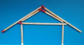 Een huis van matchsticks over blauwe achtergrond stock afbeeldingen