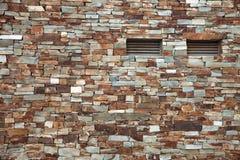 Een huisbakstenen muur met twee het luchten smalle vensters stock afbeelding