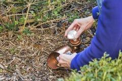 Een huiseigenaar verandert een lightbulb in openluchtverlichting Royalty-vrije Stock Foto's