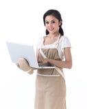 Een huisvrouw die met laptop werkt Stock Afbeeldingen