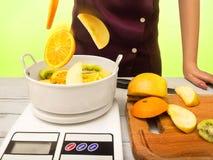 Een huisvrouwenvrouw die gesneden vruchten wegen stock foto's