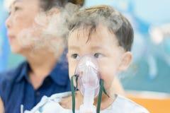 Een humeurige jongen die met een borstbesmetting na een koude of F ziek is royalty-vrije stock foto