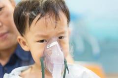 Een humeurige jongen die met een borstbesmetting na een koude of F ziek is stock fotografie
