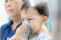 Een humeurige jongen die met een borstbesmetting na een koude of F ziek is stock foto's