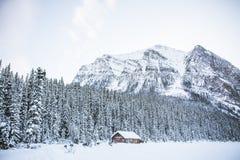 Een hut op een sneeuwgebied met rotsachtige bergen en een bos royalty-vrije stock fotografie