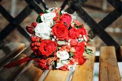 Een huwelijksboeket van rode en witte rozen op een houten bank Het bruid` s boeket royalty-vrije stock afbeelding