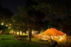 Een huwelijkstent bij nacht door bomen met een oranje gloed van de lichten wordt omringd dat - de reeks van de huwelijkstent stock afbeeldingen