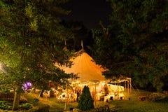 Een huwelijkstent bij nacht door bomen met een oranje gloed van de lichten wordt omringd dat - de reeks van de huwelijkstent stock afbeelding