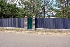 Een ijzeromheining en een groene poort dichtbij een asfaltweg Royalty-vrije Stock Fotografie