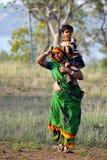 Een Indische moeder die haar dochter op haar schouder vervoeren Royalty-vrije Stock Fotografie