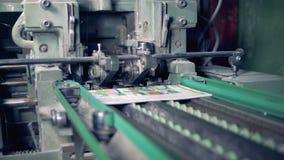 Een industriële machine snijdt randen van gedrukte tijdschriften af stock videobeelden