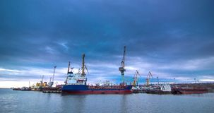 Een industriële overzeese terminal met ladingskranen en de wagens van de spoorwegcontainer bij zonsondergang De kustkraan heft vr stock video