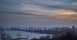 Een industriële overzeese terminal met ladingskranen en spoorwegcontainers op zonsondergang De kustkraan heft vracht tijdens op stock videobeelden