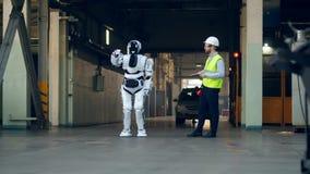Een ingenieur controleert een robot die, gebruikend een tablet werken stock video