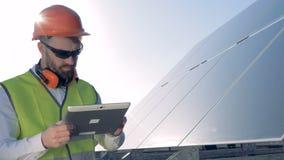 Een ingenieur controleert zonnebatterijen, omhoog sluit stock footage