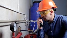 Een ingenieur in de glazenwerken in het ketelruim, controleert het onderhoud van het verwarmingssysteemmateriaal stock footage