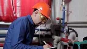Een ingenieur in de glazenwerken in het ketelruim, controleert het onderhoud van het verwarmingssysteemmateriaal stock video