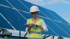 Een ingenieur werkt met apparaten, die aan een dak zich dichtbij zonnebatterijen bevinden Alternatief, groen energieconcept stock video
