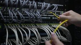 Een IT ingenieurs` s hand stopt uit de netwerkkabel van de netwerkschakelaar stock videobeelden