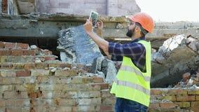 Een ingenieursbouwer in een helm berekent het plan van de de bouwvernieling en het bekijken het bouwproject op a stock video