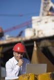 Een inspecteur van het olieplatform met zijn laptop Stock Afbeeldingen