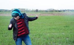 Een interessant meisje in blauw haar, luistert aan muziek en danst op het gebied stock fotografie