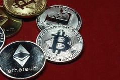 Een inzameling van cryptocurrencymuntstukken op een fluweel rode achtergrond royalty-vrije stock fotografie