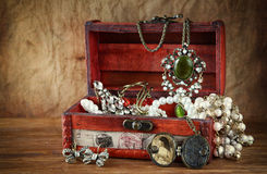 Een inzameling van uitstekende juwelen in antieke houten juwelendoos Stock Foto's
