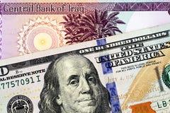Een Iraaks vijftig dinarbankbiljet met een Amerikaanse honderd dollarrekening royalty-vrije stock afbeeldingen