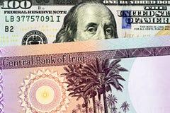 Een Iraaks vijftig dinarbankbiljet met een Amerikaanse honderd dollarrekening royalty-vrije stock foto's
