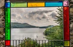 Een jacht op een meer door gekleurd glaskader dat wordt bekeken stock foto