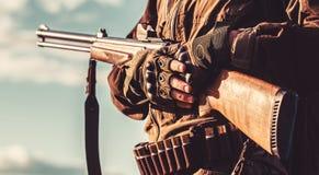Een jager met een de jachtkanon en een de jachtvorm om in een de herfstbos de man te jagen is op de jacht Jagersmens hunting stock afbeelding