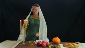 Een Jodin steekt kaarsen in een feestelijke kandelaar ter ere van Rosh Hashanah aan en leest een zegen stock videobeelden