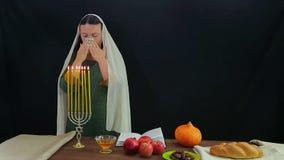 Een Jodin steekt kaarsen in een feestelijke kandelaar ter ere van Rosh Hashanah aan en leest een zegen stock footage