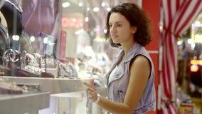 Een jong aantrekkelijk brunette bekijkt met bewondering het venster met juwelen Het meisje wil een ring of oorringen stock footage