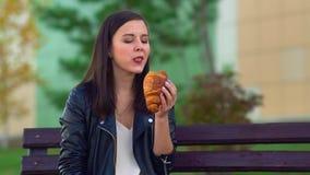 Een jong aantrekkelijk meisje dat van scones houdt Het nemen van een beet van het croissant stock video