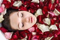 Een jong aantrekkelijk meisje neemt een badkamers met bloembloemblaadjes en ontspant tegen de achtergrond van een mooi licht stock foto